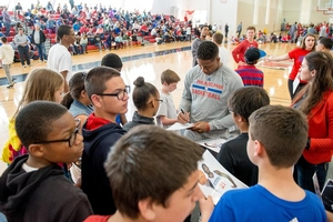 Isaiah Canaan autographs campers' player photos.