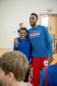Tony Wroten poses for a photo with a Sixers camper.