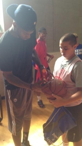 Nerlens Noel Signs basketball for overnight camper.