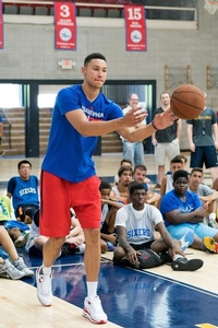 Ben Simmons passing the ball to a camper.