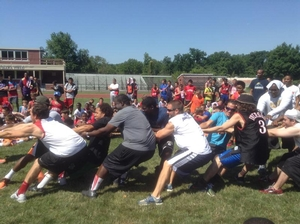 Coaches fighting to win the camper vs coaches tug of war