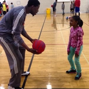 Henry Sims teaches camper ball handling drills.