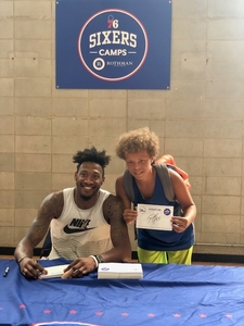 Camper receives an autograph from Robert Covington.