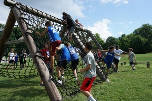 Overnight campers climbing the net wall during team Olympics.