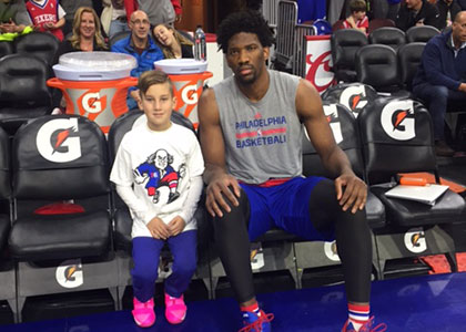 Joel Embiid with a Little Sixers Camper